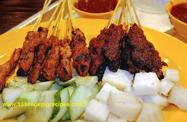 Malaysia Satay with Satay Peanut Sauce, Cucumber, Ketupat Nasi (compressed rice cakes) on the right.